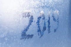 Inscription 2019 sur une fenêtre congelée dans des nombres rayés par gelée sur le fond froid bleu d'hiver photos libres de droits