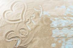 Inscription sur une plage sablonneuse sur un fond en bois clair Photographie stock libre de droits