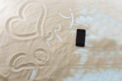 Inscription sur une plage sablonneuse sur un fond en bois clair Photos stock