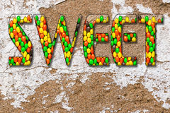Inscription. Sweet  from the multi-colored candy sweets on natural plaster wall surface Royalty Free Stock Images