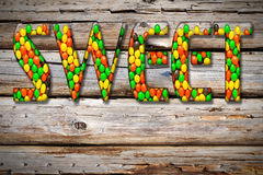 Inscription. Sweet  from the multi-colored candy sweets on wooden background Stock Photo