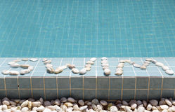 The inscription  swim  is laid out by pebble on a pool side Stock Photos