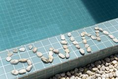 The inscription `swim` is laid out by pebble on a pool side Royalty Free Stock Photo