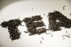 Inscription tea from black tea leaves on a white background stock photo