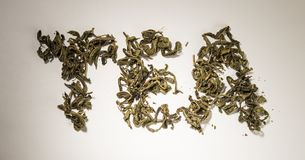 Inscription tea from green tea leaves on a white background.  stock image