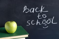 Inscription text Back to school on black chalkboard and green Apple on stack books textbooks, Concept education royalty free stock images