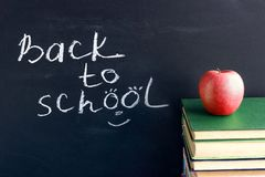 Inscription text Back to school on black chalkboard and red apple on stack books textbooks, Concept education royalty free stock photography