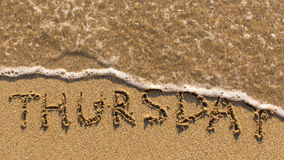 Inscription THURSDAY on a gentle beach sand with the soft wave. (days of the week series stock image