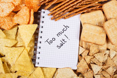 Inscription too much salt in notebook and heap of unhealthy food Stock Image