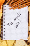 Inscription too much salt in notebook and heap of unhealthy food Royalty Free Stock Photos