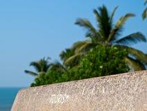 Inscription 'Tourism' on bench back. Stone bench back with inscription 'Tourism' against a tropics background Royalty Free Stock Image