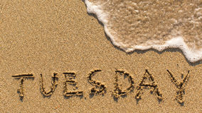 Inscription TUESDAY on a gentle beach sand with the soft wave. (days of the week series Royalty Free Stock Image