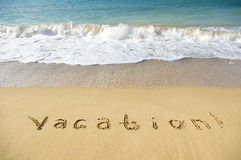 Inscription vacation on sea sand beach Royalty Free Stock Images