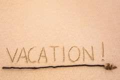 Inscription of Vacation written on wet yellow beach sand with ar Stock Photos
