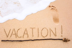 Inscription of Vacation written on wet yellow beach sand with fo Royalty Free Stock Images