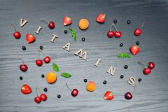 Inscription Vitamins and fruits. Black wooden background. Food c. Oncept Royalty Free Stock Image