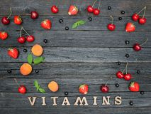 Inscription Vitamins and fruits. Black wooden background. Food c. Oncept Royalty Free Stock Photo