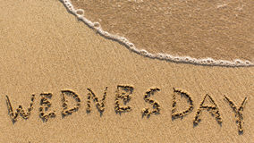 Inscription WEDNESDAY on a gentle beach sand with the soft wave. (days of the week series stock photography