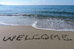 Inscription Welcome on wet sand. Stock Images