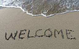 Inscription Welcome on wet sand. Royalty Free Stock Photo