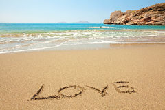 Inscription on wet sand. Love written in a sandy tropical beach Stock Photography