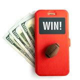 Inscription WIN on the smartphone screen. The concept of winning sports betting. A ball for American football or rugby and a. Mobile phone in a red case lies on royalty free stock photos