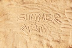 Inscription word summer and hand prints on sand. stock photography