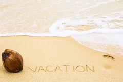 Inscription of word Vacation written on wet yellow beach sand, f Royalty Free Stock Photos