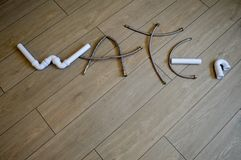 The inscription, the word water made of white, water, plastic pipes and made up of metal hoses. Royalty Free Stock Image