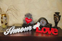 Wooden inscription with the words love in the room on the dresser