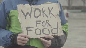 The inscription `Work for food` by the poor homeless tramp. Kyiv. Ukraine