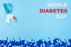 Inscription world diabetes day, blue ribbon awareness with red blood drop and line of lancets on a blue background. Inscription world diabetes day blue ribbon stock illustration