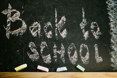 Chalk with words back to school. An inscription written in chalk back to school on an old blackboard royalty free stock photos
