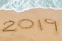 2019 inscription written on sandy beach with wave approaching Stock Photos