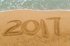 2017 inscription written on sandy beach with wave approaching Stock Photography