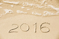 2016 inscription written in the wet yellow beach sand being wash Stock Image