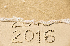 2015 2016 inscription written in the wet yellow beach sand being Stock Photos