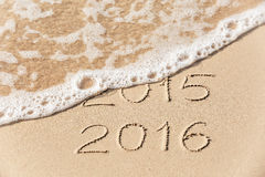 2015 2016 inscription written in the wet yellow beach sand being. Washed with sea water wave. Concept of celebrating the New Year at some exotic place Royalty Free Stock Images