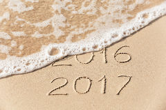 2016 2017 inscription written in the wet yellow beach sand being Stock Image