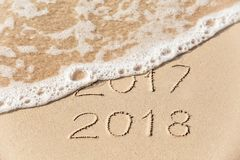 2017 2018 inscription written in the wet yellow beach sand being Stock Image