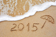 Inscription of the year 2015 written in the wet yellow beach sa Stock Photo
