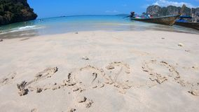 The inscription with your finger on the sand 2020. Tropical white sand beach, waves, boats swing. Sunny weather, blue sky. The inscription with your finger on stock video