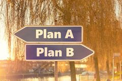 Two blue arrows in the opposite direction with the inscription Plan A and Plan B with sunny background of a city stock images