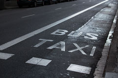 Inscriptions taxi and bus on the roadway Royalty Free Stock Photography