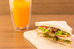 Insect food. Sandwich made of fried insect meat and mozzarella cheese, mayonnaise and tomato, lettuce with orange juice presented on a wooden board. Close-up Royalty Free Stock Photo