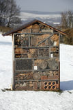 Insect hotel in winter. Insect hotel created from natural materials with nesting facilities during winter; shelter and refuge for many types of insects like Stock Photography
