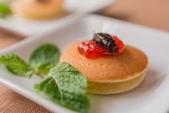 Insect pancake. Cricket insect with sweet strawberry jam on a pancake and mint leaf for breakfast. Close-up, Selective focus Royalty Free Stock Images