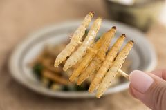 Insectes de nourriture : L'insecte en bambou de Caterpillar de ver de participation de la main de la femme a fait frire croustill image stock