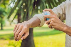 Insectifuge de pulvérisation de moustique de jeune homme dans le forrest, protection d'insecte image libre de droits