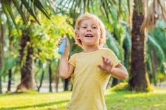 Insectifuges de pulvérisation de garçon sur la peau photo stock